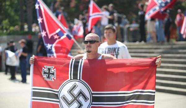 A protester stands with a Nazi flag during a rally at the South Carolina Statehouse in 2015. Image by Max Blau.