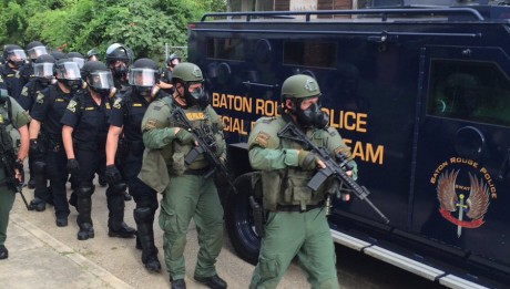 Riot police with assault weapons walk alongside an armored urban assault vehicle equipped with an LRAD sound cannon in Baton Rouge, LA.  Credit: @rebekahallen
